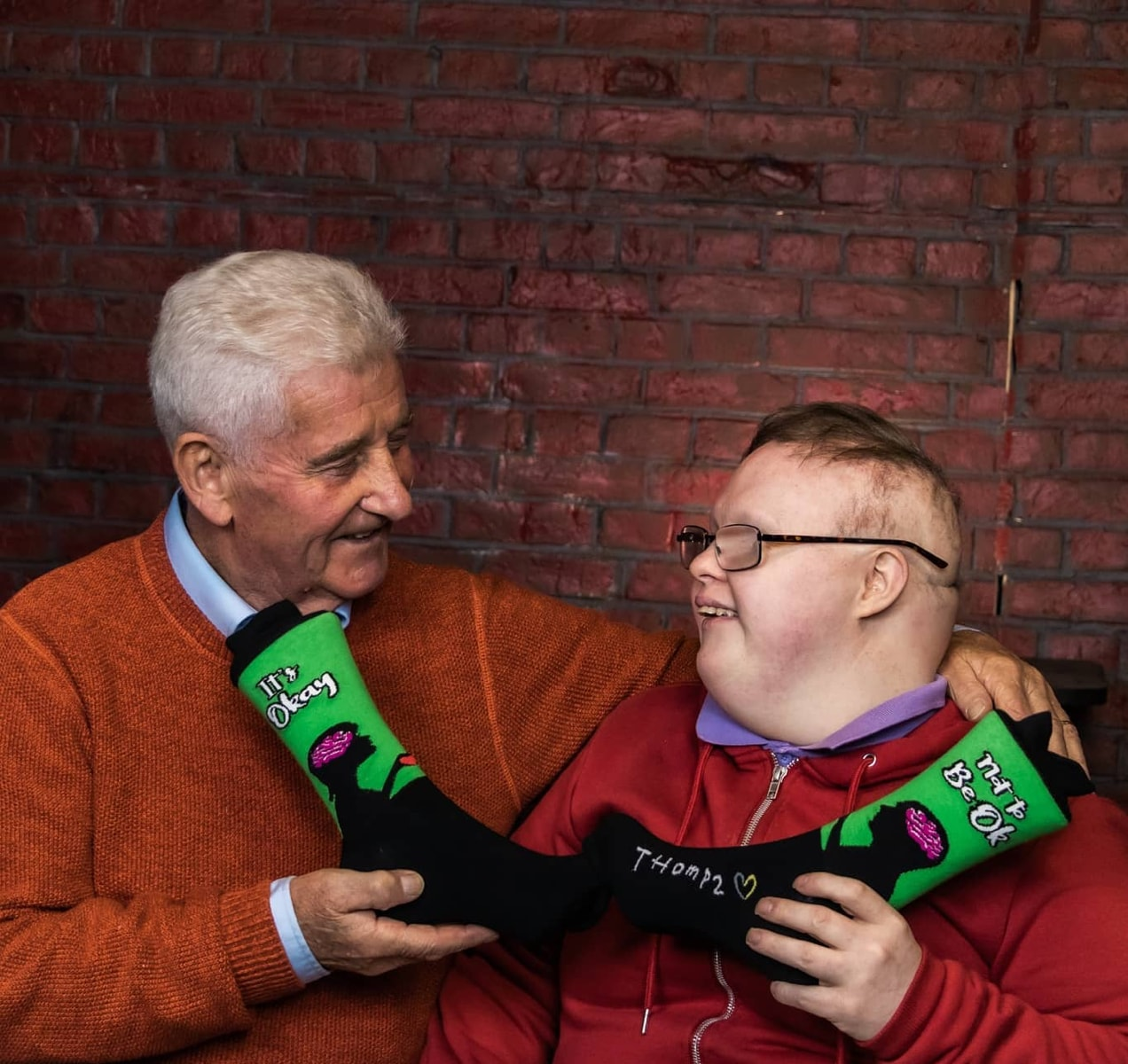 Thomas and his father with a pair of socks that say,